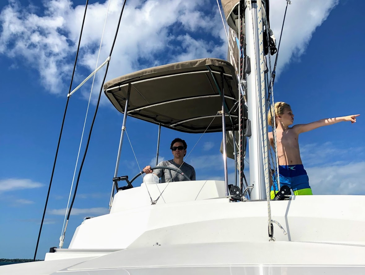 Brian and son skippering their bareboat catamaran in the Bahamas