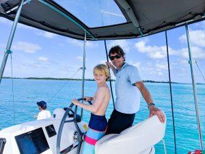Brian and son steering a bareboat catamaran charter
